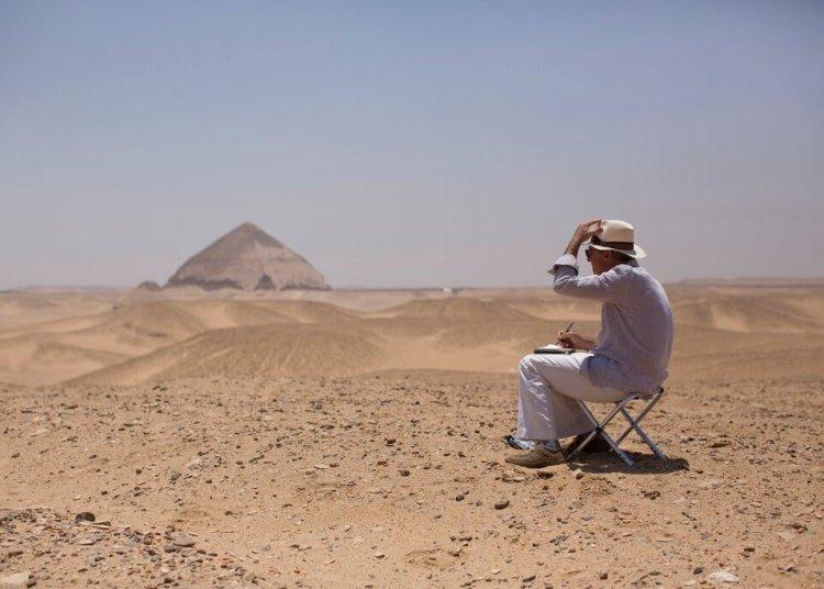 Un miembro de una delegación internacional dibuja el sitio de la Pirámide de Bent durante un evento de apertura para los visitantes de la pirámide y sus entornos en Dashur, Egipto, el sábado 13 de julio de 2019. Foto AP/Maya Alleruzzo.