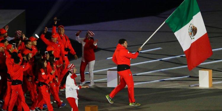 El tirador mexicano Jorge Orozco porta la bandera de su país en la ceremonia inaugural de los Juegos Panamericanos de Lima, el viernes 26 de julio de 2019 (AP Foto/Silvia Izquierdo)