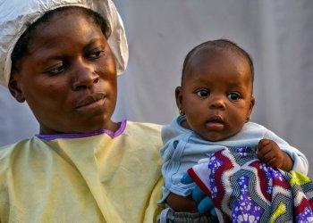 En esta image, tomada el 17 de julio de 2019, Lahya Kathembo, de dos meses, espera en los brazos de una enfermera a los resultados de una prueba de ébola en un centro de tratamiento de la enfermedad en Beni, República Democrática del Congo. (AP Foto/Jerome Delay)