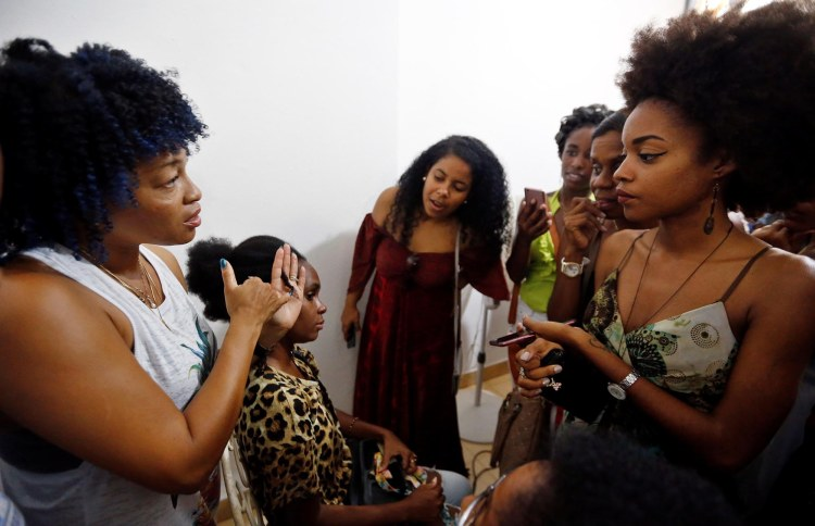 """Erlys Pennycook (i), emprendedora y creadora de línea de productos para el cabello """"Que Negra"""", realiza demostraciones de peinados el pasado 29 de junio del 2019, en La Habana. Foto: Ernesto Mastrascusa / EFE."""