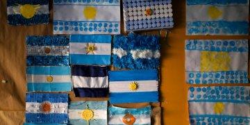 Banderas argentinas están en una pared en una escuela usada como casilla para votar durante las elecciones primarias en Buenos Aires, Argentina, el domingo 11 de agosto de 2019. (AP Foto/Natacha Pisarenko)