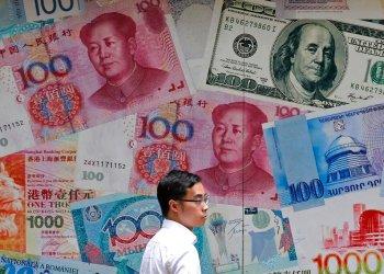 Un hombre camina frente a una casa de cambio decorada con distintos billetes en el distrito financiero de Hong Kong. (AP Foto/Kin Cheung, Archivo)