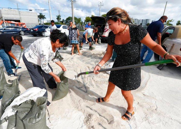 Georgia Bernard (derecha) y Ana Pérez, junto a otros residentes, llenan sacos de arena para llevárselos a casa antes de la llegada del potente huracán Dorian, el 30 de agosto de 2019, en Hallandale Beach, Florida. Foto: Wilfredo Lee/ AP.