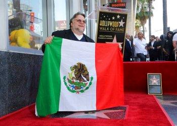 El cineasta mexicano Guillermo del Toro posa con la bandera de México tras una ceremonia en su honor para develar su estrella en el Paseo de la Fama de Hollywood el martes 6 de agosto de 2019 en Los Angeles. Foto: Willy Sanjuan/Invision/AP.