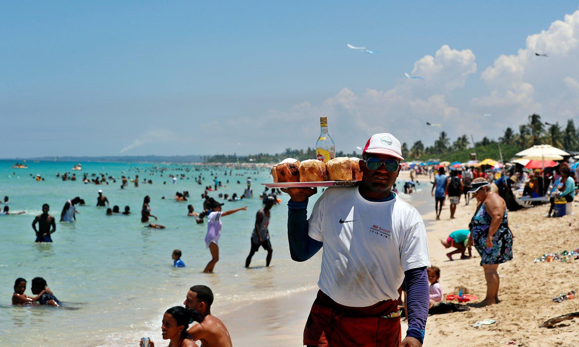 Un hombre vende agua de coco con ron a los bañistas en una playa del litoral norte de La Habana este verano. Foto: Ernesto Mastrascusa / EFE.