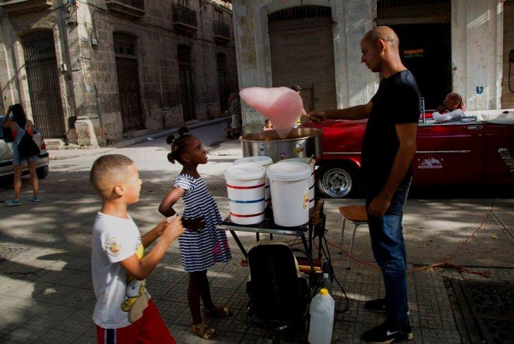 Una niña observa a un vendedor de algodones de azúcar en la Habana Vieja, Cuba, en agosto de 2019. Foto: Ismael Francisco / AP.