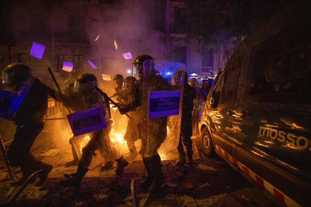 Policías con equipo antimotines pasan por una barricada en llamas durante choques con manifestantes en Barcelona, España, el martes 15 de octubre de 2019. Foto: Emilio Morenatti / AP.