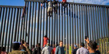 Un grupo de inmigrantes intenta saltar el muro metálico en la frontera con San Diego. Foto: Joebeth Terrique/EFE.