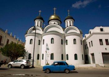 Un auto Moscovich de la era soviética circula por delante de entrada la catedral ortodoxa rusa de La Habana. Foto: Ismael Francisco/AP.
