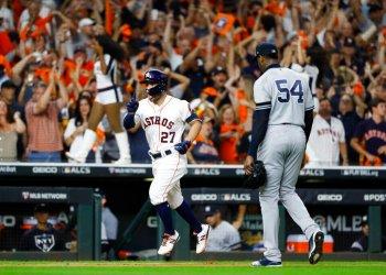 El cubano Aroldis Chapman, de los Yanquis de Nueva York, se marcha del terreno, mientras el venezolano José Altuve, de los Astros de Houston, festeja un jonrón en el sexto juego de la Serie de Campeonato de la Liga Americana, el sábado 19 de octubre de 2019. Foto: Matt Slocum/AP.