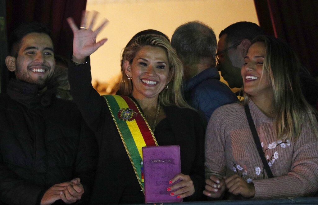 La segunda vicepresidenta del Senado de Bolivia y senadora de la oposición Jeanine Áñez, en el centro, saluda a la multitud ataviada con la banda presidencial en el balcón del palacio de Quemado, tras proclamarse presidenta interina del país, en la Paz, Bolivia, el martes 12 de noviembre de 2019. Foto: Juan Karita / AP.