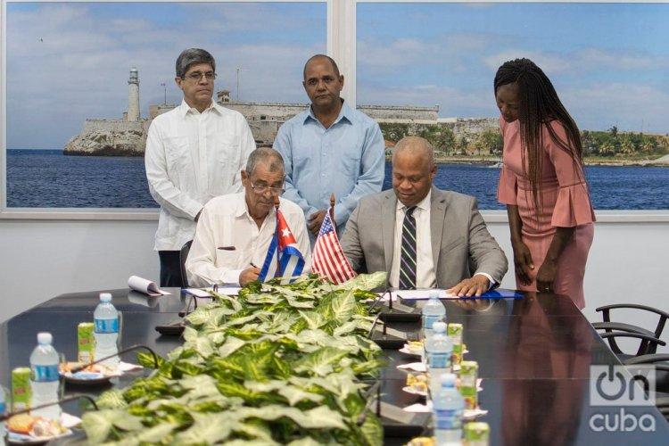 Arthur C. Walton (d), director de Relaciones Intergubernamentales de la ciudad de Nueva Orleans, y Félix Mejías (i), director de Relaciones Internacionales de la Asamblea Provincial de La Habana, firman un memorando de entendimiento entre las dos ciudades, en La Habana, el 14 de noviembre de 2019. Detrás, Carlos Fernández de Cossío (i), director general para Estados Unidos de la Cancillería cubana; Reinaldo García Zapata (c), presidente de la Asamblea Provincial de La Habana; y Rosine Pema Sanga (d), directora de Relaciones Internacionales de New Orleans. Foto: Otmaro Rodríguez.