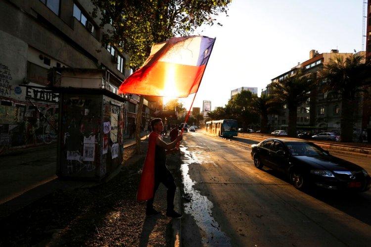 Un manifestante contra el gobierno ondea una bandera chilena durante una protesta en Santiago de Chile el lunes 16 de diciembre de 2019. Foto: Fernando Llano / AP.