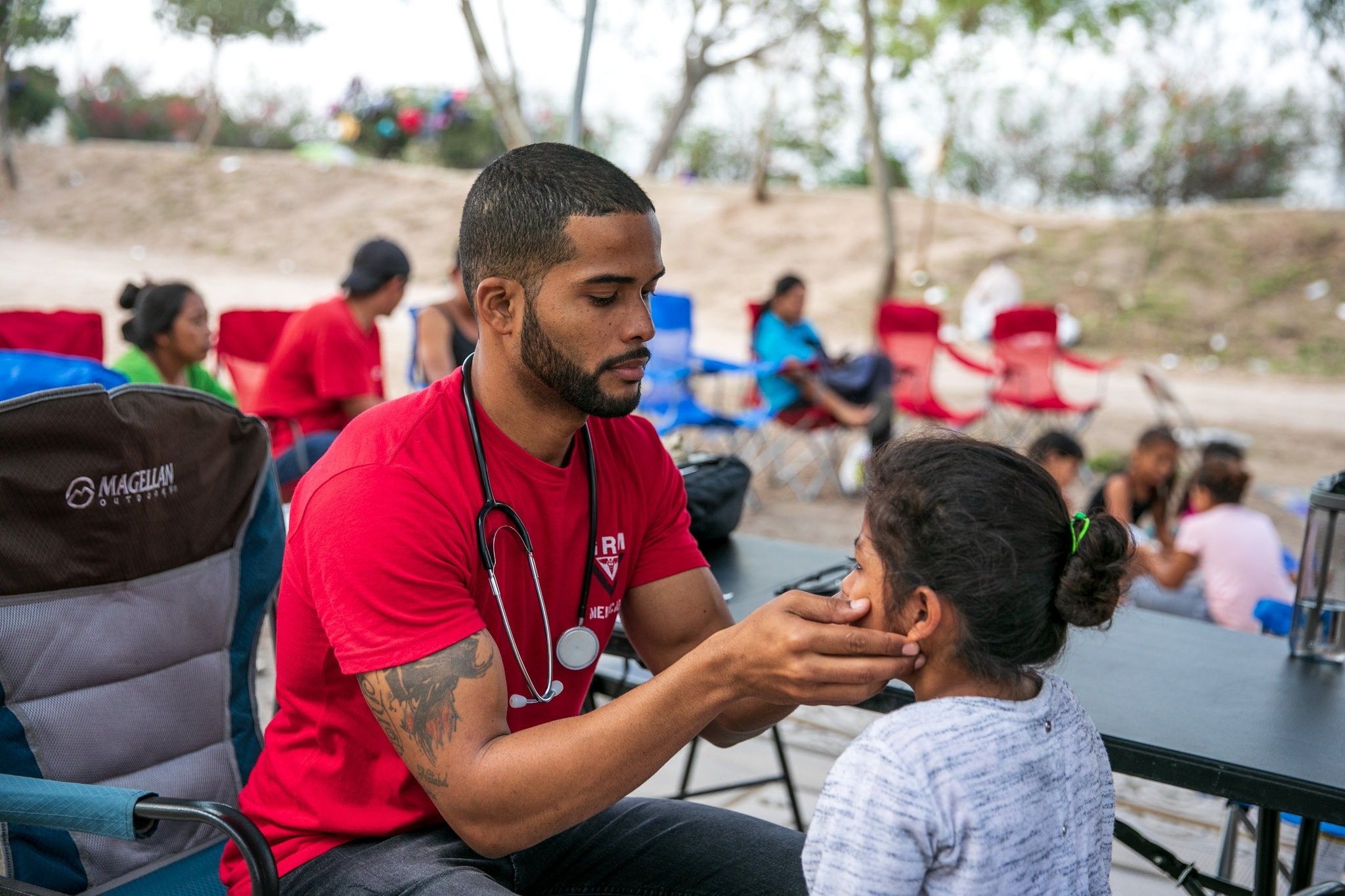 El médico cubano Dairon Elisondo trata a una niña en un campamento de migrantes en Matamoros, México. Foto: Ilana Panich-Linsman / The New York Times.