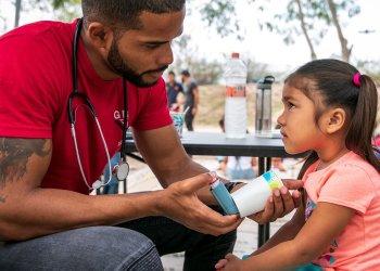 El médico cubano Dairon Elisondo trata a una niña de 4 años, enferma de asma, en un campamento de migrantes en Matamoros, México. Foto: Ilana Panich-Linsman / The New York Times.