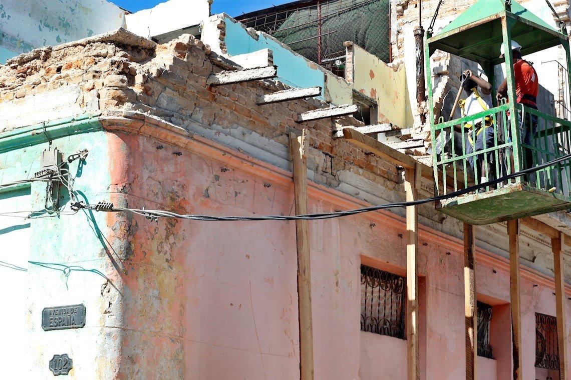 Dos personas trabajan el martes 28 de enero de 2020, en el lugar donde murieron tres niñas, de 11 y 12 años, al derrumbarse el balcón de un edificio, en el barrio de Jesús María, en la Habana Vieja. Foto: Ernesto Mastrascusa / EFE.