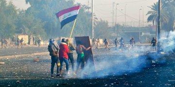 Manifestantes ondeando la bandera nacional mientras las fuerzas de seguridad lanzan gas lacrimógeo a una protesta en el centro de Bagdad, Irak, el lunes 20 de enero de 2020. Foto: AP/Hadi Mizban