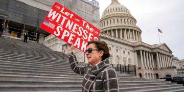 Laura Albinson muestra un cartel mientras abandona el Capitolio, en Washington, el viernes 10 de enero de 2020. (AP Foto/J. Scott Applewhite)