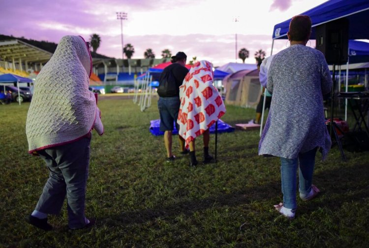 Varias personas se ponen de pie luego de pasar la noche en un estadio de béisbol tras un sismo de magnitud 6,4 en Guayanilla, Puerto Rico, el viernes 10 de enero de 2020. Foto: AP/Carlos Giusti