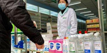 Una farmacéutica atiende a clientes en la entrada de una tienda en Beijing, China, el 20 de febrero de 2020. Foto: Ng Han Guan / AP.