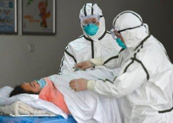 Personal sanitario provisto con trajes protectores traslada a una paciente infectada con coronavirus a un pabellón de aislamiento en el Segundo Hospital del Pueblo en Fuyang, provincia de Anhui, en el centro de China. Foto: Chinatopix vía AP.