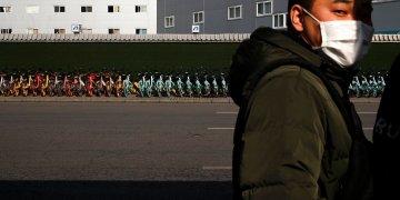 Un hombre con mascarilla junto a una fila de bicicletas de alquiler estacionadas ante una estación de metro en Beijing, el lunes 10 de febrero de 2020. (AP Foto/Andy Wong)