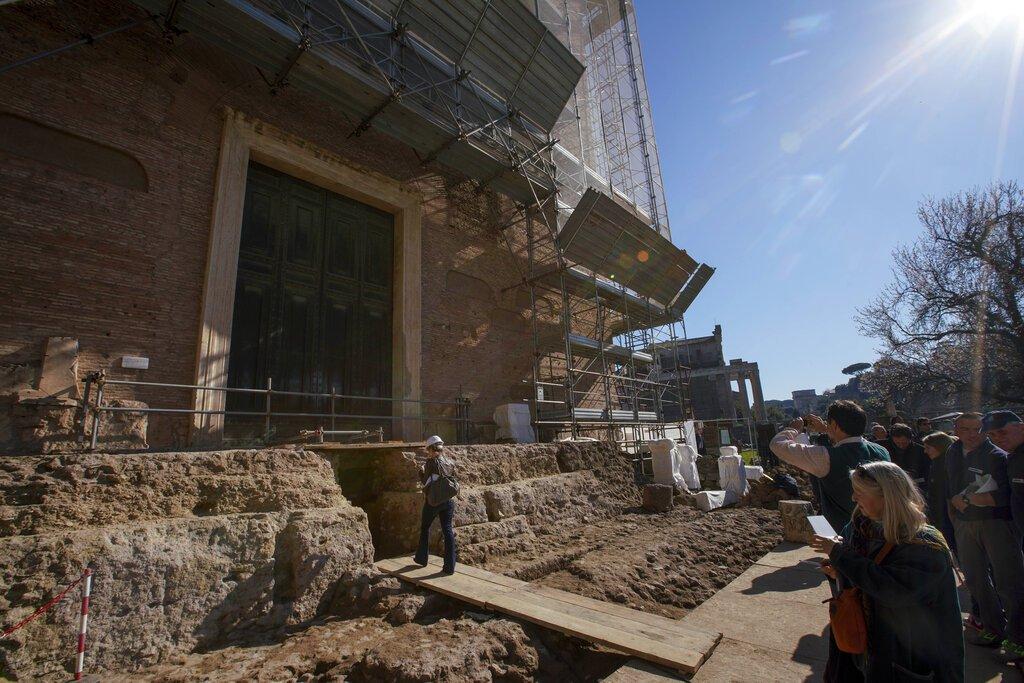 Reporteros esperan a entrar a la cámara subterránea donde se encontró un sarcófago de 1,4 metros y lo que parece ser una pieza de un altar del siglo VI a.C. en el antiguo Foro Romano, durante una presentación a los medios en Roma, el viernes 21 de febrero de 2020. Foto: Andrew Medichini / AP.