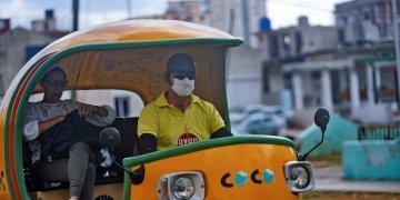 Un chofer de cocotaxi usa un nasobuco como medida de protección contra el coronavirus, en La Habana. Foto: Yander Zamora / EFE.