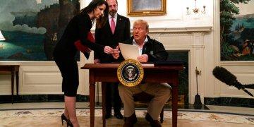 El secretario de Salud y Servicios Humanos, Alex Azar, al fondo, observa cómo la asistente Catherine Bellah Keller entrega documentos al presidente Donald Trump para que firme un proyecto de ley de gastos para combatir el coronavirus. Foto: Evan Vucci/AP.