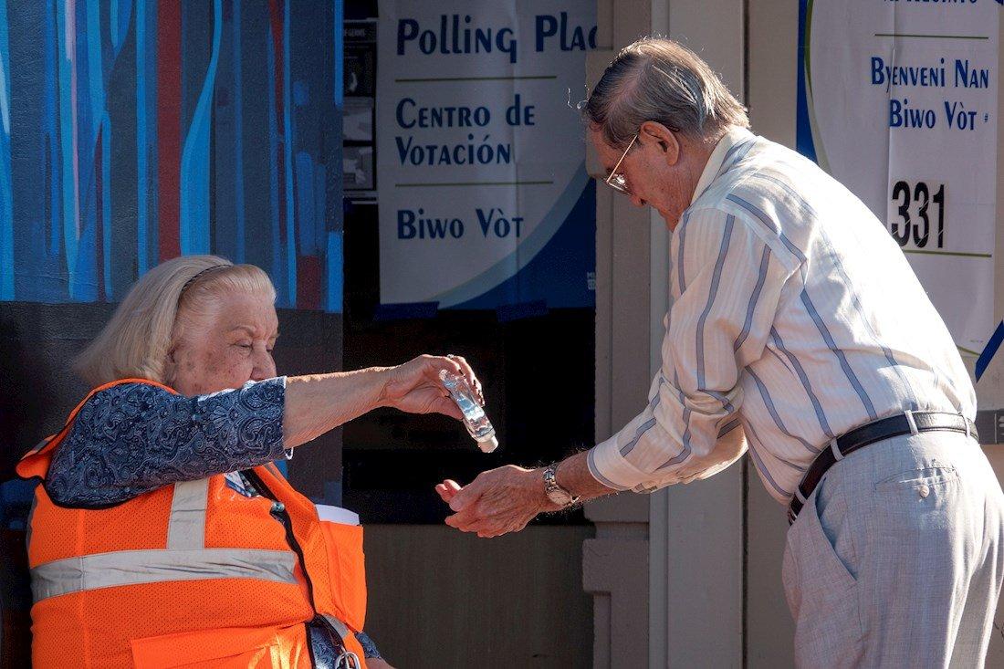 Una trabajadora de un colegio electoral echa desinfectante en las manos de un votante antes de que emita su voto en las elecciones primarias en Miami, Florida, el 17 de marzo de 2020. Foto: Cristóbal Herrera / EFE.