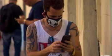 Un cubano revisa su celular usando un nasobuco en La Habana, como medida de protección frente a la pandemia de COVID-19. Foto: Otmaro Rodríguez.