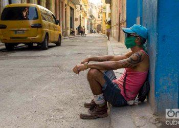 Un hombre sentado en una acera de La Habana, con un nasobuco como medida de protección contra la pandemia de coronavirus. Foto: Otmaro Rodríguez.