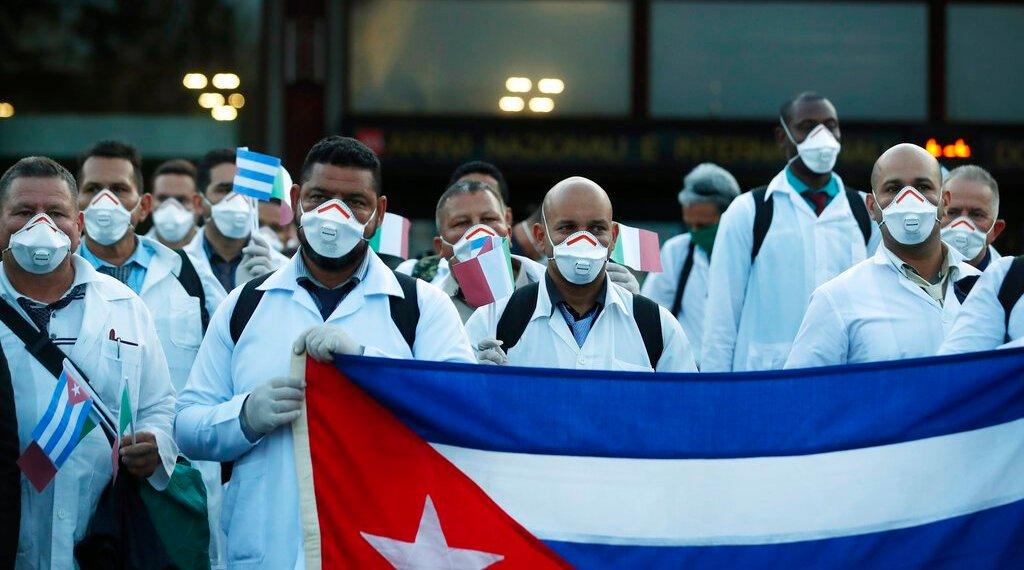 Personal médico cubano posa a su llegada al aeropuerto Malpensa de Milán, Italia, el domingo 22 de marzo de 2020, para ayudar en la atención a los enfermos de covid-19. Foto: AP / Antonio Calanni.