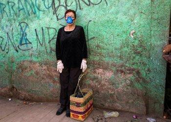 Carmen Villanueva, con una máscara de respirador y guantes desechables, espera a su hija durante un viaje de compras a un mercado popular en Lima, Perú, el sábado 4 de abril de 2020. Debido a la emergencia de salud por la propagación del nuevo coronavirus, el gobierno está restringiendo el movimiento de las personas por género. Foto AP/Rodrigo Abd.