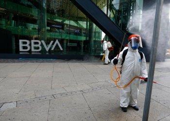Trabajadores municipales rocían desinfectante frente al edificio del banco BBVA sobre la avenida Paseo de la Reforma en la Ciudad de México. Foto: Rebecca Blackwell/AP.