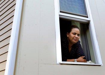 En imagen del miércoles 20 de mayo de 2020, Wendy De Los Santos, originaria de la República Dominicana, posa para una fotografía desde una ventana de su hogar, en Malden, Massachusetts. (AP Foto/Steven Senne)