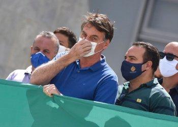 El presidente Jair Bolsonaro tocándose su nasobuco durante una protesta contra el Supremo Tribunal Federal y el Congreso Nacional en Brasilia. Foto: André Borges/AP.