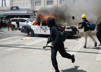 Agentes antidisturbios en Los Ángeles, California, se enfrentaron con manifestantes que incendiaron al menos dos patrullas y dañaron a otros. Foto: AP.