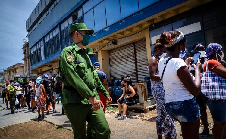 Un soldado vigila afuera de una tienda estatal de comida donde las personas esperan en línea para entrar en La Habana, Cuba, el martes 19 de mayo de 2020. Foto: AP/Ramon Espinosa.