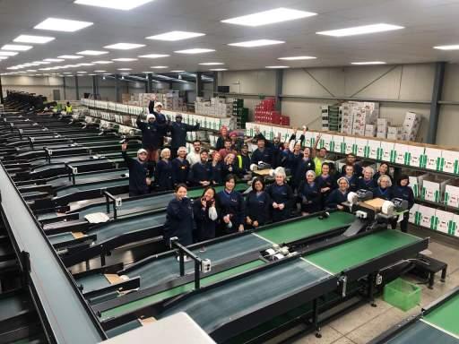 travailleurs dans une usine d'emballage de pommes