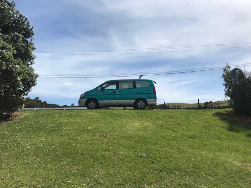 van serena vert de côté sur une route avec un champ vert devant