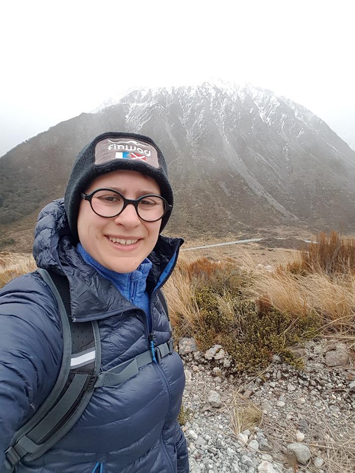 portrait d'une femme en doudoune et bonnet en randonnée montagne nouvelle-zelande
