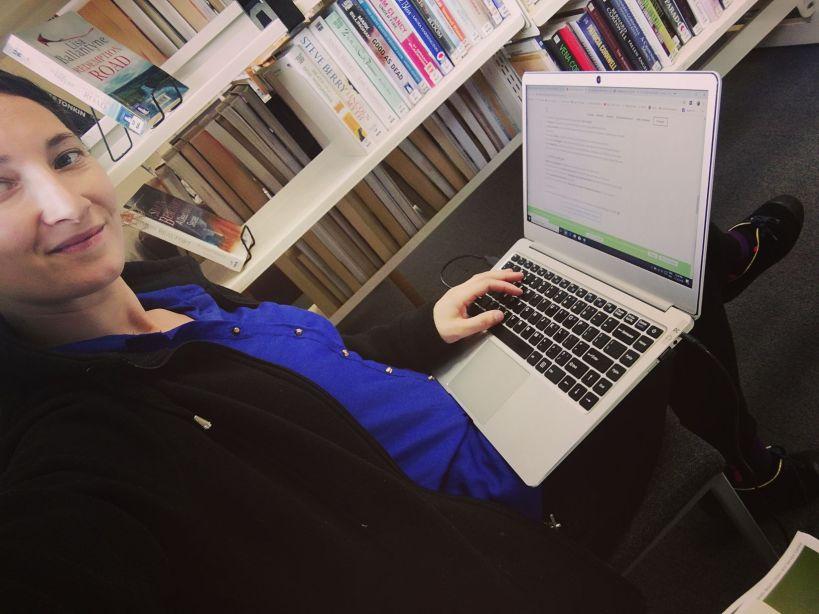 femme digital nomade avec un ordinateur dans une bibliothèque