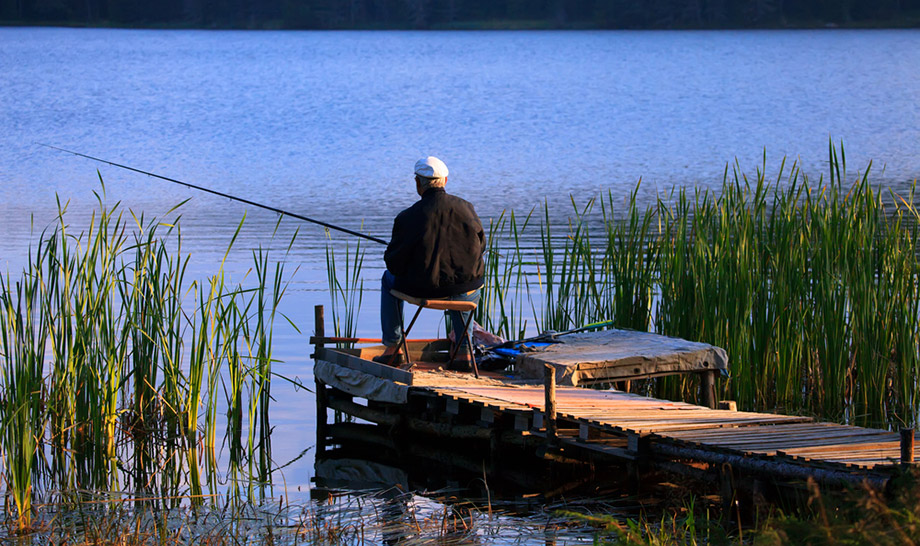 man fishing on lake