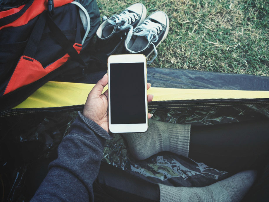 Woman Holds Phone Out While Camping