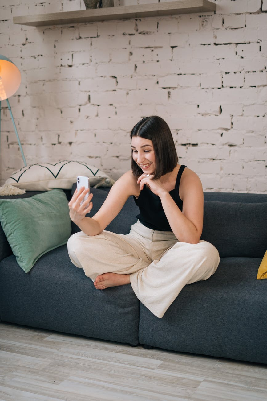 woman in black tank top and white pants sitting on gray couch