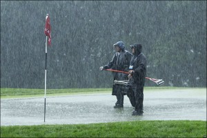 These gents seem to be willing to battle the rain for the sake of golf, but oddly ill-equipped for the task.