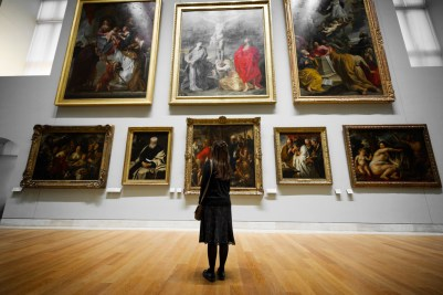 Picture of a woman looking at a wall of paintings