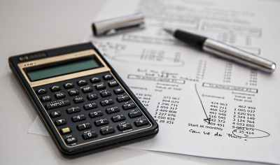 Caption: Picture of a calculator and an accounting financial statement