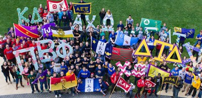 students in greek life organizations holding their letters